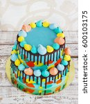 Small photo of 2-tiered homemade children's cake decorated with colorful daub on white background.