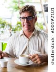 Small photo of Adult male having a hot coffee in the morning while making bad taste face expression
