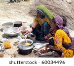 Small photo of HYDERABAD, PAKISTAN - AUG 27: A flood affectee prepares food for her family at a flood relief camp on August 27, 2010 in Hyderabad.