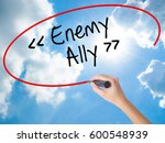 Small photo of Woman Hand Writing Enemy - Ally with black marker on visual screen. Isolated on Sunny Sky. Business concept. Stock Photo
