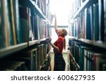 woman taking book from library... | Shutterstock . vector #600627935