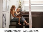 mother with baby reading book.... | Shutterstock . vector #600630425