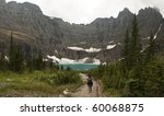 Small photo of One hiker walking towards Iceberg Lake in Glacier National Park. The headwall of the valley is a perfect bowl formed by cliffs with hanging glaciers; the ice calves off to form icebergs in the lake.