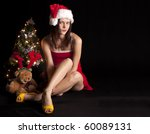 Sexy young woman with red dress and Christmas hat sitting next to a small Christmas tree and a teddy bear, isolated on a black background. - stock photo