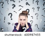 Small photo of Portrait of a stressed teen girl sitting near a gray wall with question marks falling aground her. Concept of too many questions.