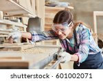 woman as joiner grinding wood | Shutterstock . vector #601002071