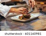 chef in restaurant arrangin and ... | Shutterstock . vector #601160981
