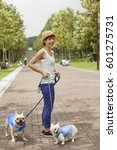 Stock photo woman walking two dogs on a paved path 601275731
