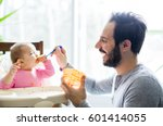 a father feeding his little... | Shutterstock . vector #601414055