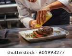 chef in restaurant arrangin and ... | Shutterstock . vector #601993277