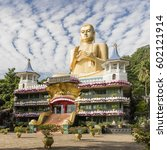 Small photo of Dambulla, Sri Lanka - 13 December 2015: Garish, modern Buddhist temple with colossal Buddha statue located at the access to ancient Dambulla Cave temples photographed in bright sun with broken clouds