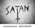 Small photo of Text Satan an upturned christian cross - writing and symbol on the cracked wall. Sign and expression of satanism. Black and white pictures with dark corners (vignetting)