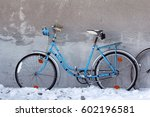 An Old Blue Bicycle Against A...
