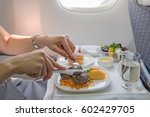 Small photo of woman eats lunch in travel aboard of international flight