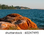 Round rocks on Georgian Bay covered by a red lichen - stock photo
