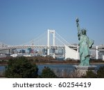Lady liberty juxtaposed against Rainbow Bridge in Tokyo, Japan. - stock photo