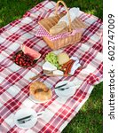 Small photo of Delicious healthy spread for a summer picnic with croissants, baguette, fresh fruit and cheese arranged on a red and white checkered rug on green grass with a wicker hamper