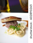 Small photo of grilled beef tenderloin medallions ,served roasted Foie gras with homemade ravioli with red wine sauce on white plate