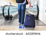 Traveler with a bag at the speedwalk - stock photo