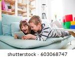 happy siblings lying on sofa at ... | Shutterstock . vector #603068747