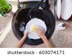 child hands scrubbing a plate... | Shutterstock . vector #603074171
