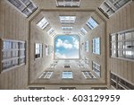 Small photo of Looking up at the sky framed by a building, freedom and entrapment conceptual picture.