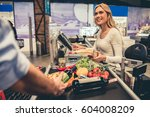 Small photo of Beautiful young cashier is smiling while working at the supermarket