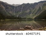 Small photo of Avalanche Lake in Glacier National Park. The headwall of the valley is in the background with several waterfalls that are cascading down the cliffs from glaciers above.