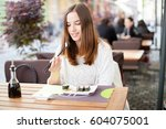 young woman eating sushi... | Shutterstock . vector #604075001