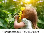 happy little girl smelling a... | Shutterstock . vector #604101275