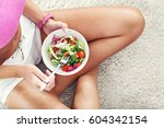 fit woman eating healthy salad... | Shutterstock . vector #604342154