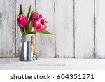 pink tulips in a rustic metal... | Shutterstock . vector #604351271