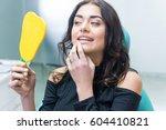 woman checking teeth in mirror. ... | Shutterstock . vector #604410821