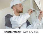 young contractor installing... | Shutterstock . vector #604472411