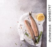 Stock photo freshly salted herring with salt lemon ans rosemary on gray background with copy space 604485797