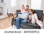 smiling family sitting on grey...   Shutterstock . vector #604530911