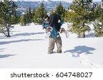 a man in deep snow carrying a... | Shutterstock . vector #604748027