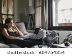 a woman at home on the sofa... | Shutterstock . vector #604754354