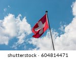 swiss flag with cloudy sky   Shutterstock . vector #604814471