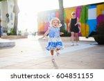 a little girl in a blue dress... | Shutterstock . vector #604851155