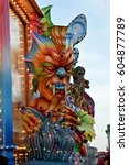 Small photo of Acireale (CT), Italy - February 28, 2017: detail of a allegorical float depicting a colorful demon emerging from colored flames, during the carnival parade along the streets of Acireale.