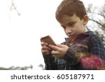 a young boy outside playing...   Shutterstock . vector #605187971