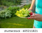 woman holding a plate with...   Shutterstock . vector #605211821