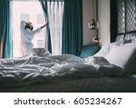 Stock photo woman meets rainy morning in luxus hotel room 605234267