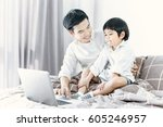 father and son using laptop in... | Shutterstock . vector #605246957