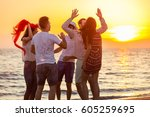young people dancing on beach... | Shutterstock . vector #605259695