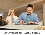 young business couple signing a ...   Shutterstock . vector #605354819