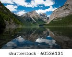 Reflection of tree covered and snow peaked Mt. Robson in Kinney Lake on a summer