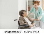 pretty young caregiver helping... | Shutterstock . vector #605414915