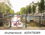 Stock photo pink bicycle on a bridge among the canals of amsterdam at sunset 605478389